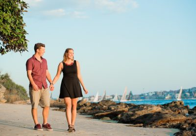 A young couple walk along a small beach for their Sydney Harbour Engagement photoshoot
