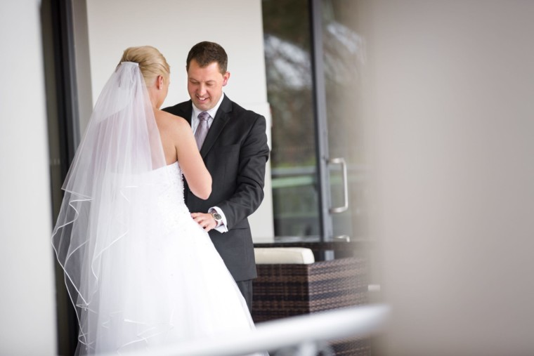 groom examines brides dress after their first look