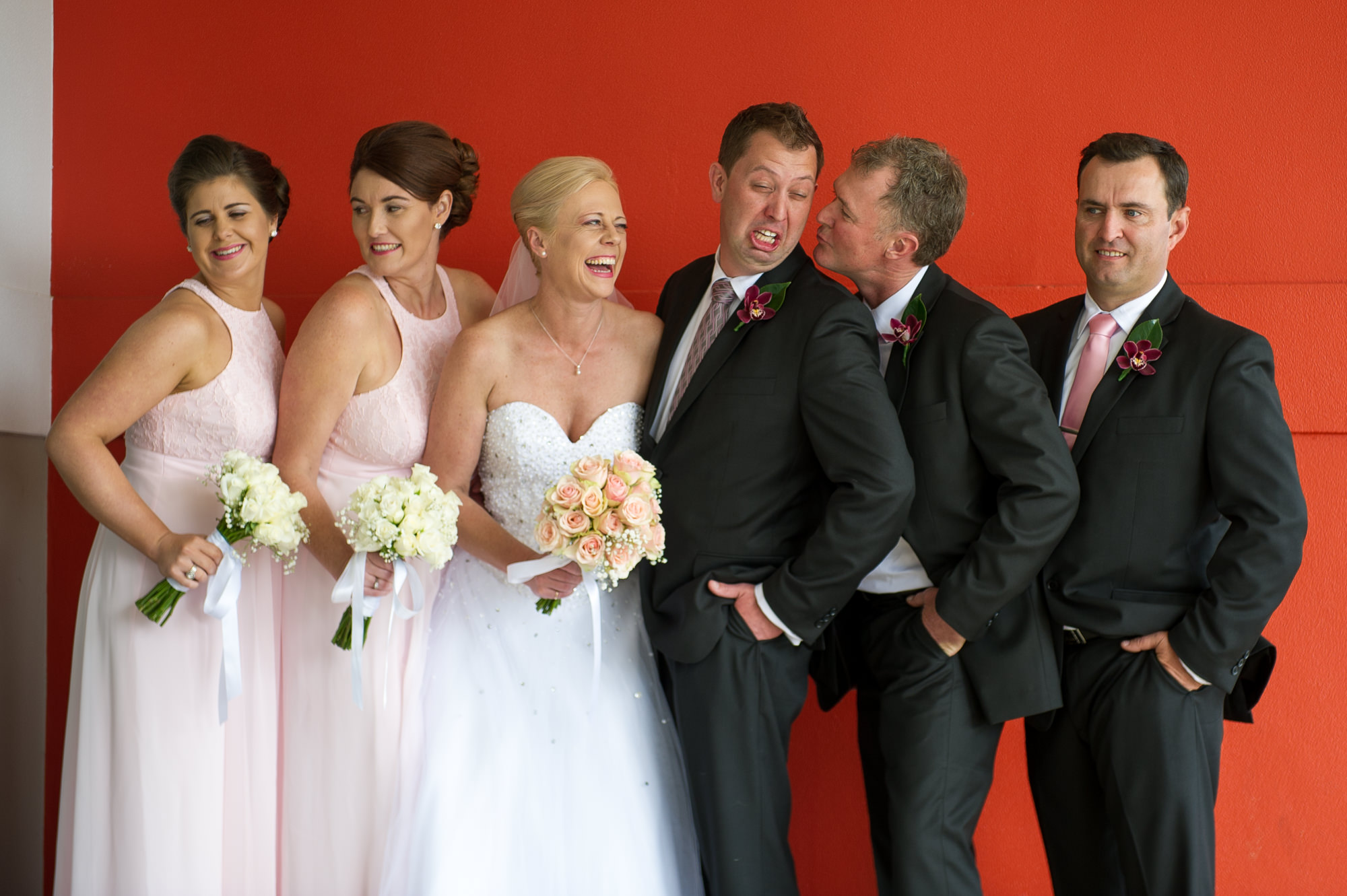 Bridal party fun photo with men pulling funny faces and women laughing