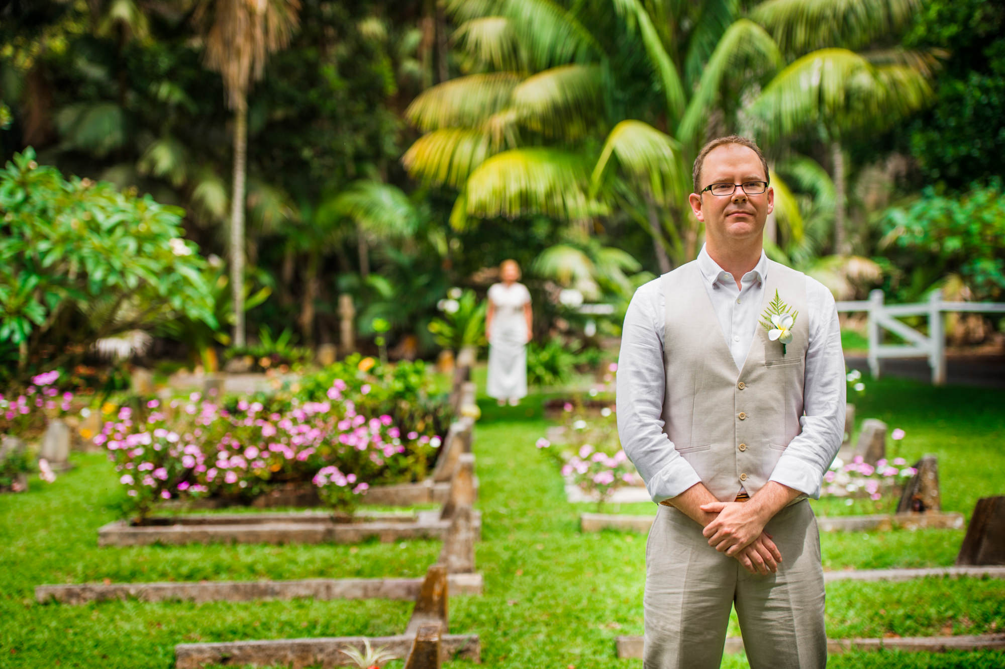 groom waits patiently whilst bride is in the distance behind him at the Lord Howe Island cemetery