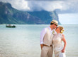 bride and groom kiss standing in shallow water with a cloud misted Mount Gower in the distance
