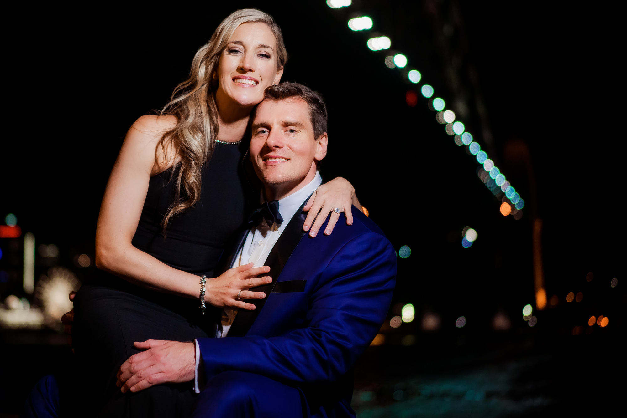 engaged couple in formal wear sit in front of the Harbour Bridge for their engagement photos
